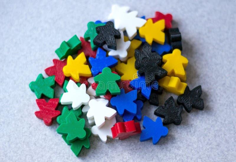 Grupper av färgrika meeplesdelar av leken på grå bakgrund Små diagram av mannen Begrepp för brädelekar Lycka och gyckel royaltyfri bild