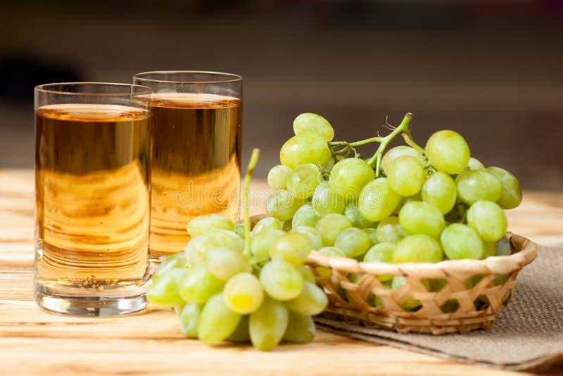 Grupper av nya mogna gröna druvor i vide- korg på stycke av säckväv och två exponeringsglas med druvafruktsaft på trätexturerade  arkivbild