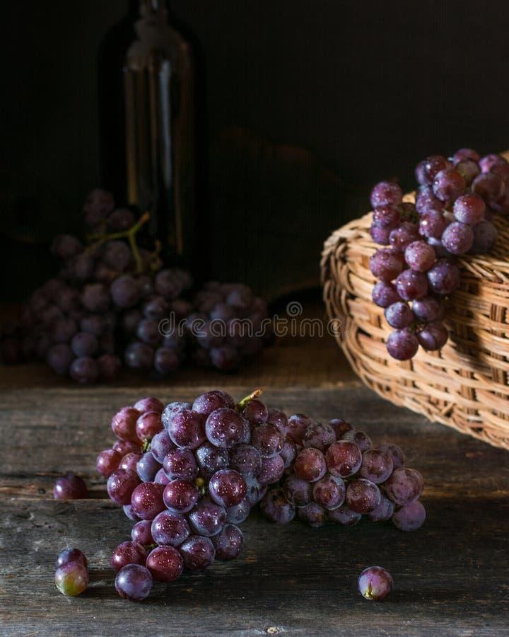 Grupper av nya mogna röda druvor på en trätextural yttersida Filial av rosa druvor druvarött vin mörka druvor Stilleben av arkivfoto
