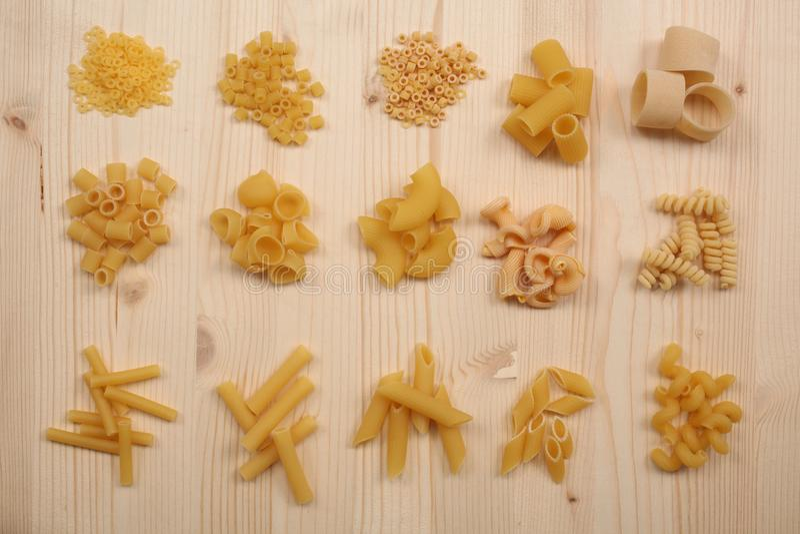 Grupper av olika sorter av torr okokt pasta på en trätabell fotografering för bildbyråer