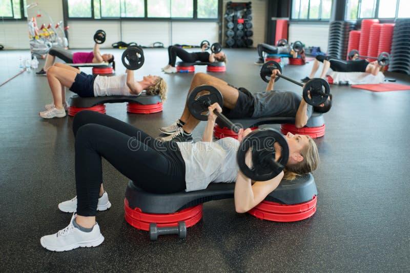 Gruppera folk som gör kondition som tillsammans övar i idrottshall royaltyfri foto