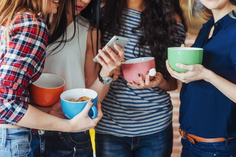 Gruppera härliga ungdomarsom tycker om i konversation och dricker kaffe, bästa vänflickor som har tillsammans gyckel arkivfoto