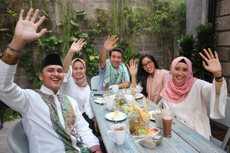 Gruppera lyckliga unga muslim som vinkar på tabellen som äter middag under ramadan c royaltyfri fotografi