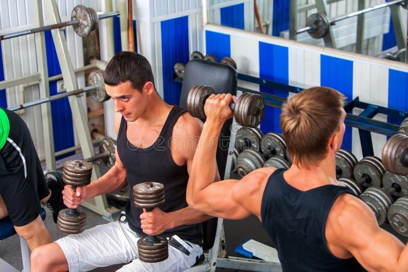 Gruppera män som arbetar hans armar med hantlar på idrottshallen royaltyfri fotografi