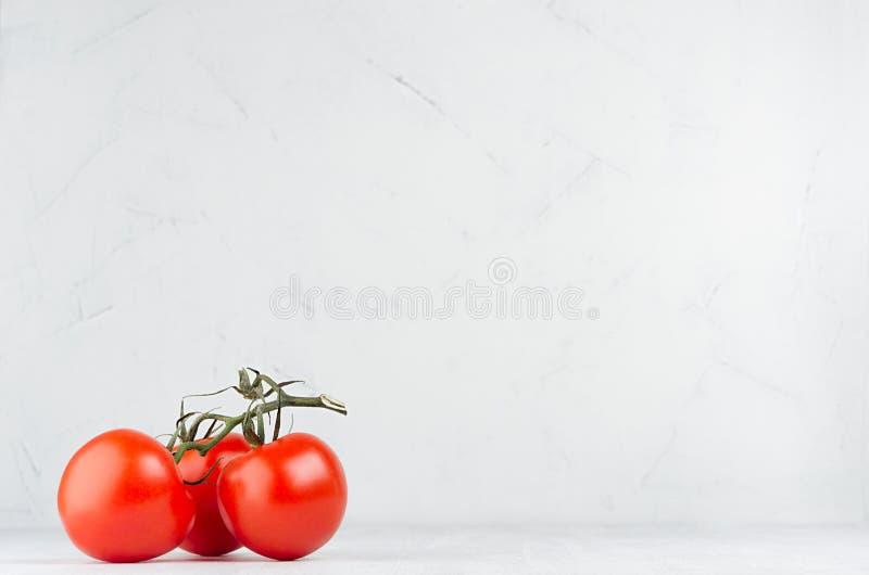 Gruppera mogna röda glansiga tomater på grön filial på vit träbakgrund, kopieringsutrymme royaltyfri foto