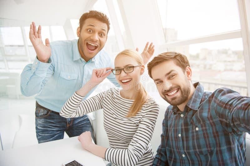 Gruppera skottet av kollegor som har gyckel i deras kontor royaltyfri foto