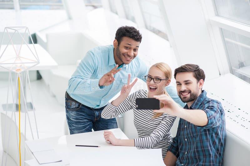 Gruppera skottet av kollegor som har gyckel i deras kontor royaltyfria foton