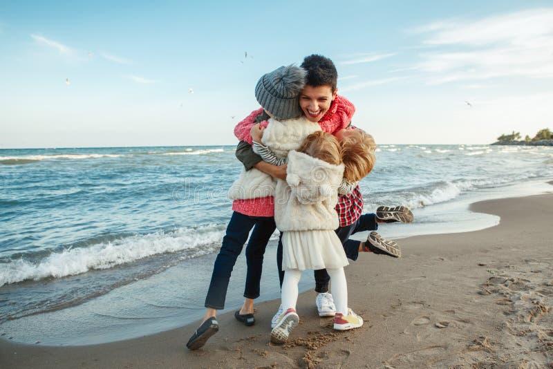 Gruppera ståenden av den vita Caucasian familjen, moder med tre barnungar som kramar le att skratta på havhavsstranden på solnedg arkivbild