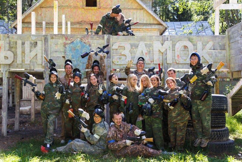 Gruppera ståenden av det stora lyckliga företaget som spelar paintball royaltyfri foto