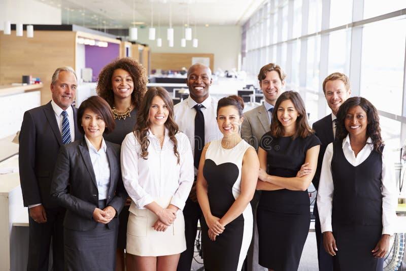 Gruppera ståenden av ett lag av att le kontorscoworkers arkivfoto