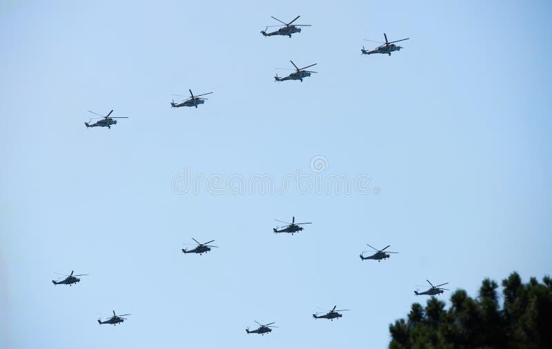 Gruppera stridhelikoptrar i flykten under en militär demonstrati arkivbilder