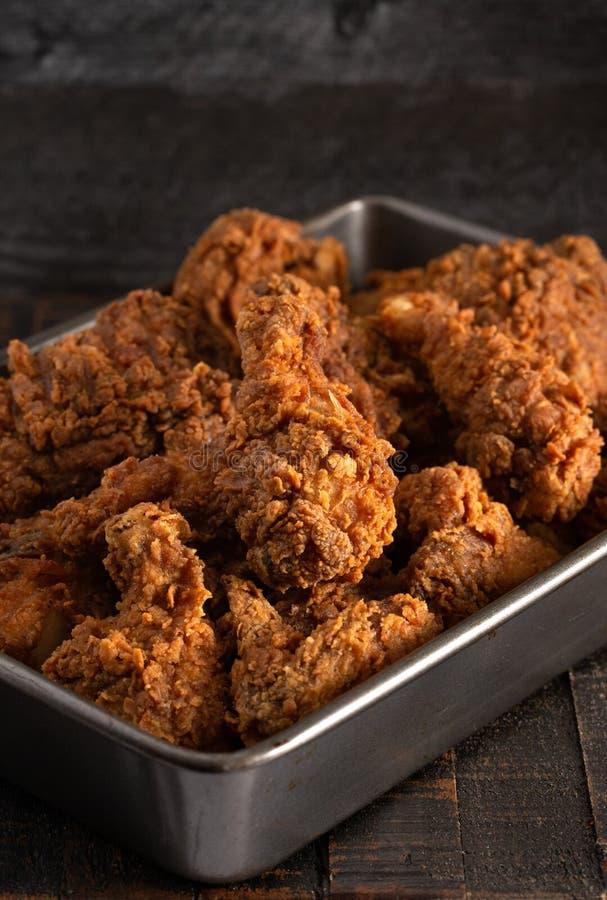 Gruppering av frasiga hemlagade Fried Chicken på en lantlig trätabell arkivbilder