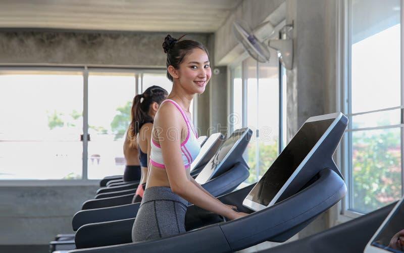 Gruppfolket joggar på en konditiontrampkvarn Ungdomarru royaltyfri bild