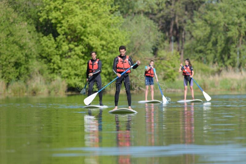 Gruppfolket står paddleboarding upp royaltyfria foton