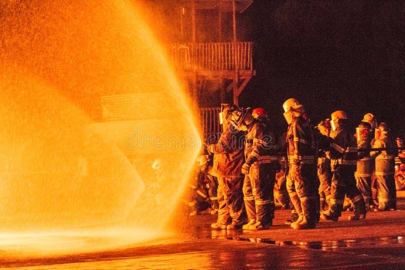 Gruppi dei pompieri che lavorano ad un fuoco immagini stock libere da diritti