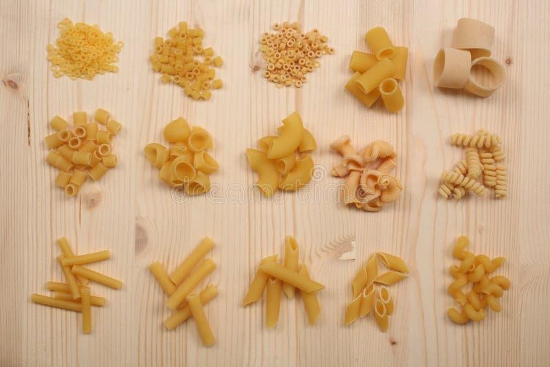 Gruppi di generi differenti di pasta cruda asciutta su una tavola di legno immagine stock