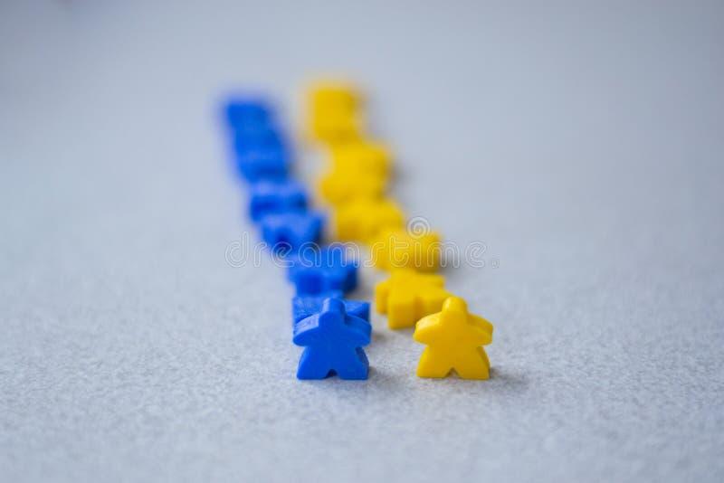 Gruppi di meeples variopinti di due gruppi Colori della bandiera ucraina - blu e gialla Piccole figure dell'uomo fotografia stock