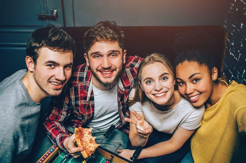Gruppieren Sie Bild von glücklichem Menschen vier, das sich entschied, zusammen den ganzen Tag zu bleiben, wenn es Raum spielte D stockbilder