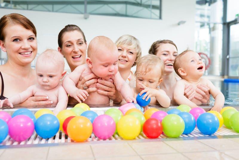 Gruppieren Sie Bild von Müttern und von Babys am Säuglingsschwimmkurs lizenzfreie stockbilder