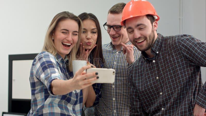 Gruppieren Sie das selfie, das von den Kollegen geschossen wird, die Spaß in ihrem Büro haben lizenzfreie stockfotos