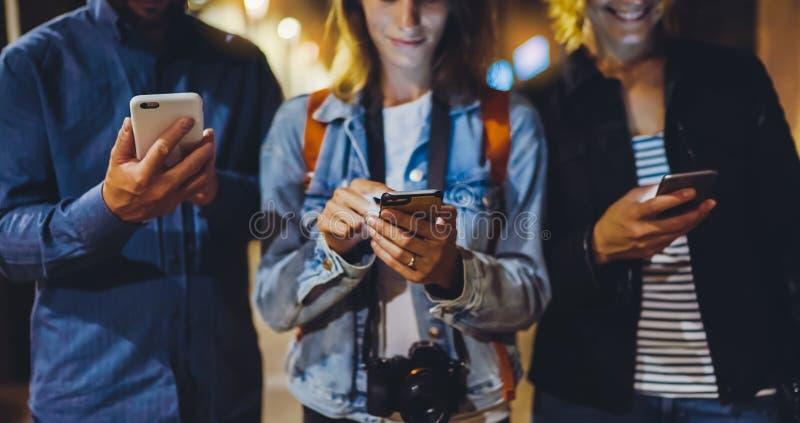 Gruppieren Sie die erwachsenen Hippies, die in der Hand-Handynahaufnahme, Straßenon-line--Wi-Fiinternet-Konzept verwenden, die zu stockfotos