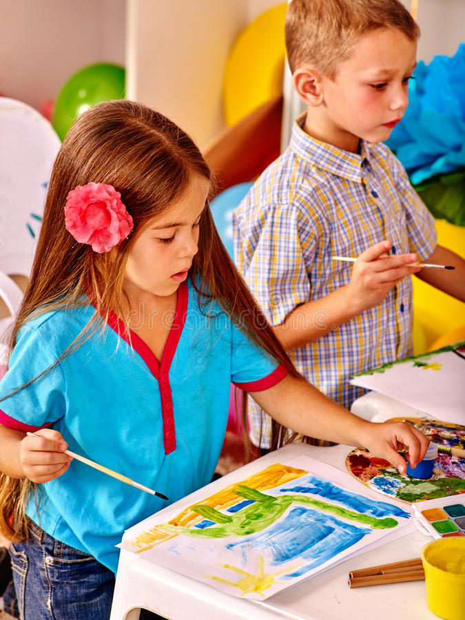 Gruppieren Sie kleines Mädchen mit Bürstenmalerei im Kindergarten stockfotografie