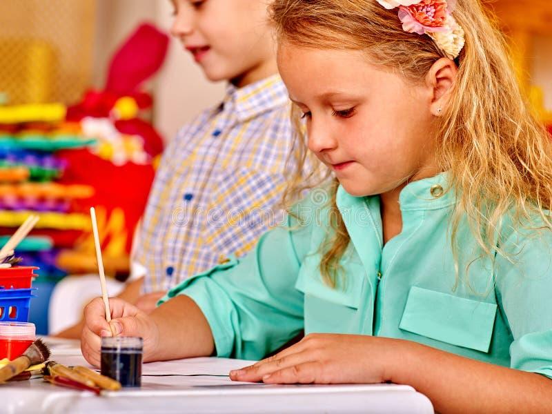 Gruppieren Sie kleines Mädchen mit Bürstenmalerei im Kindergarten stockbilder