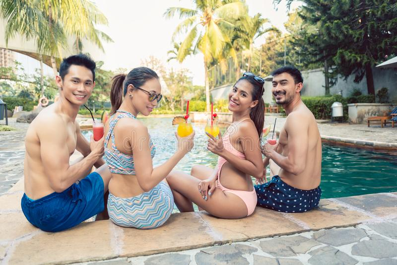 Gruppieren Sie Porträt von vier jung und von trinkenden Cocktails der schönen Leute lizenzfreie stockfotos