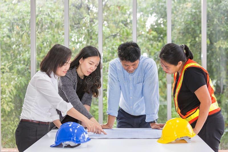 Gruppingenjörer som arbetar i mötesrum på kontoret Arbetare i teamet talar om byggplan Elektrisk matarmatur eller arkivbild