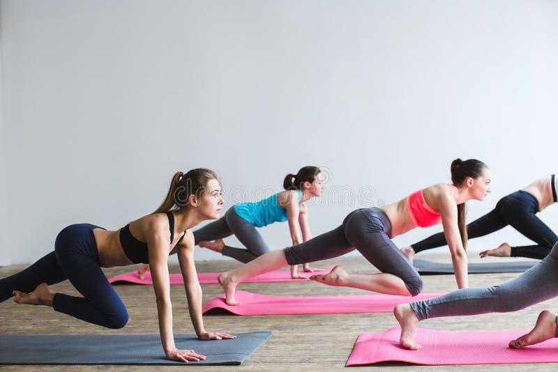 Gruppkvinnor på golv av sportar att göra som för idrottshall skjuter, ups royaltyfria bilder