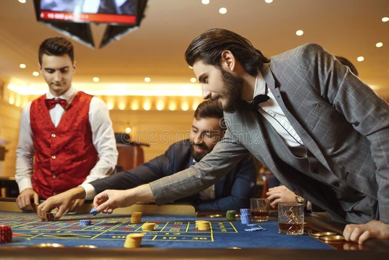 Gruppmanhasardspelare i en dräkt på tabellrouletten som spelar poker på en kasino royaltyfria bilder