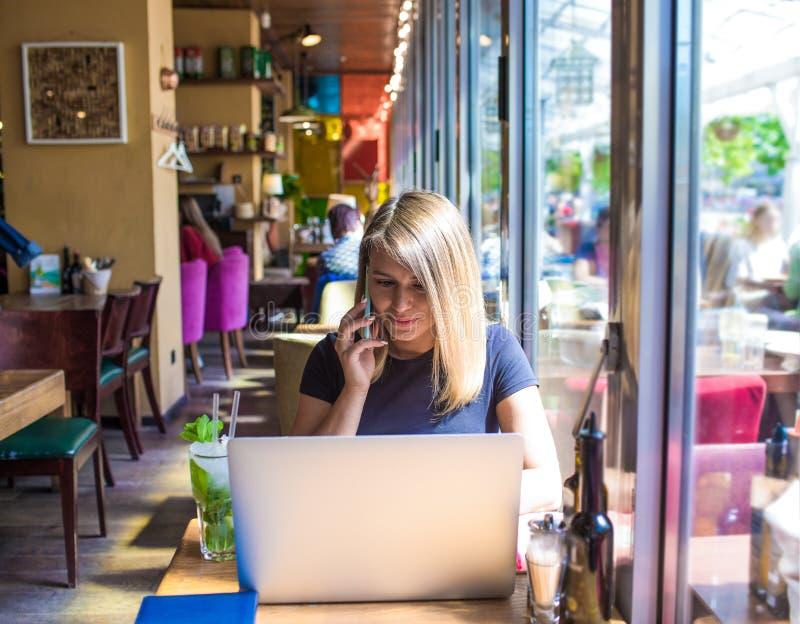 Gruppo admin della donna nella rete sociale che chiama tramite cellulare durante il lavoro sul taccuino fotografie stock libere da diritti