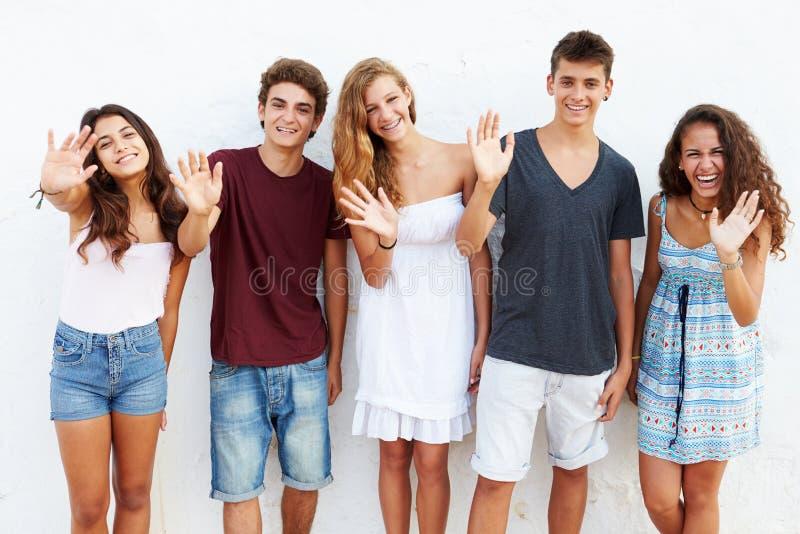 Gruppo adolescente che pende contro l'ondeggiamento della parete fotografia stock