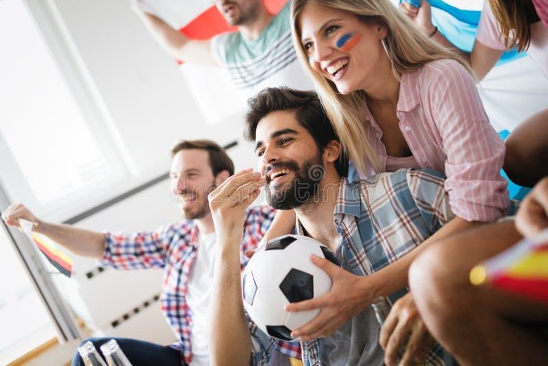 Gruppo allegro di amici che guardano partita di football americano sulla TV fotografie stock