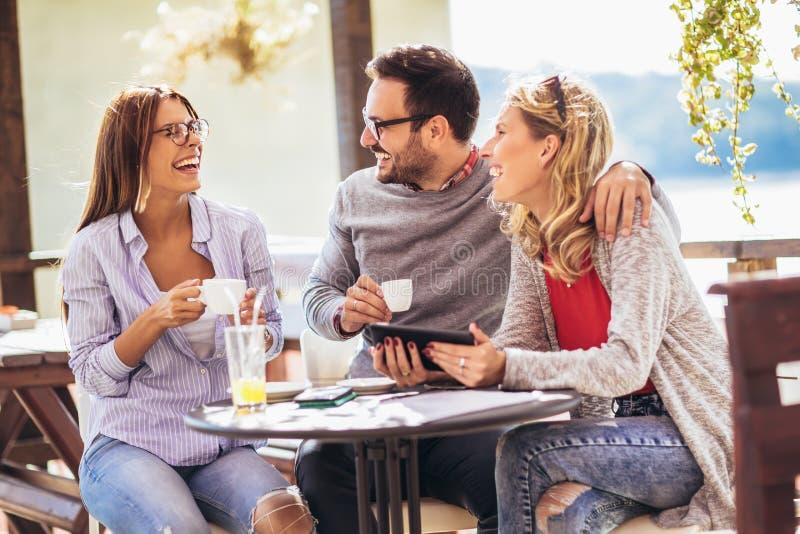 Gruppo allegro di amici divertendosi in caffè immagini stock libere da diritti