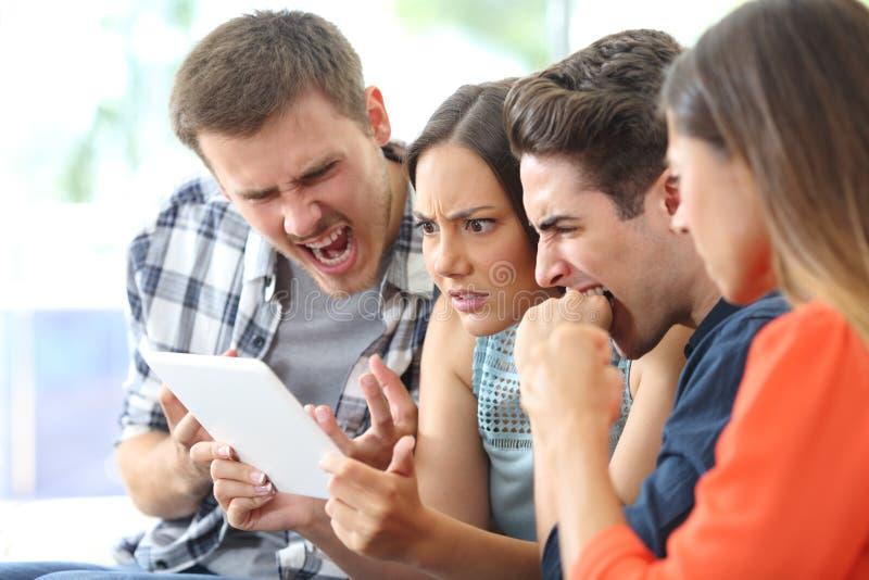 Gruppo arrabbiato di amici che guardano media sulla compressa fotografia stock libera da diritti