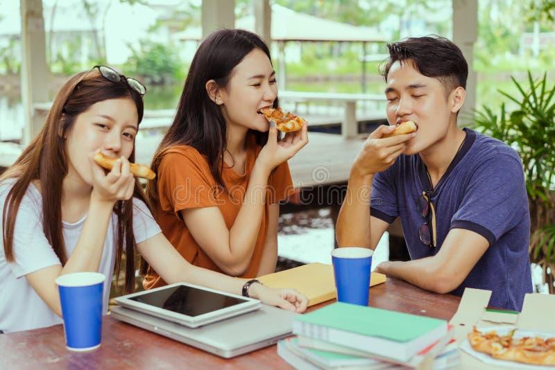 Gruppo asiatico che mangia insieme pizza nella rottura del tempo fotografie stock libere da diritti