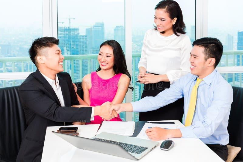 Gruppo asiatico del banchiere che consiglia le coppie in ufficio fotografie stock libere da diritti