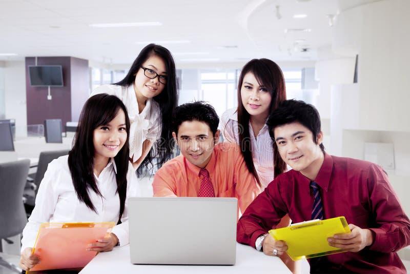 Gruppo asiatico di affari con il computer portatile immagini stock