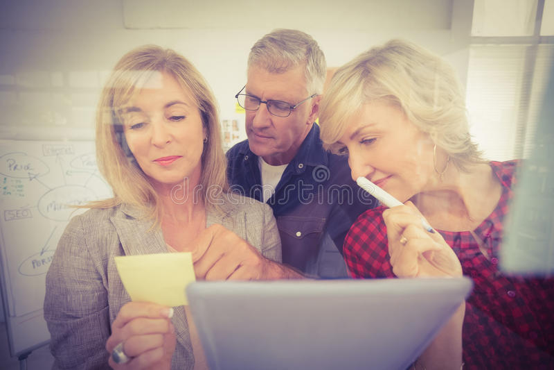 Gruppo attento di affari che esamina un Post-it immagine stock