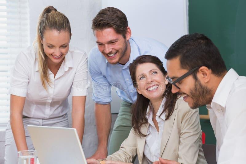 Gruppo casuale di affari che ha una riunione facendo uso del computer portatile fotografie stock