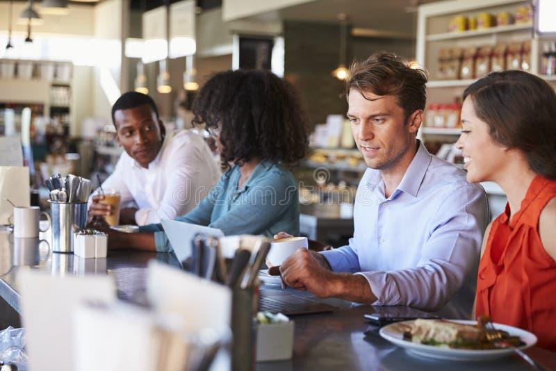 Gruppo che gode del pranzo di lavoro al contatore delle specialità gastronomiche immagini stock