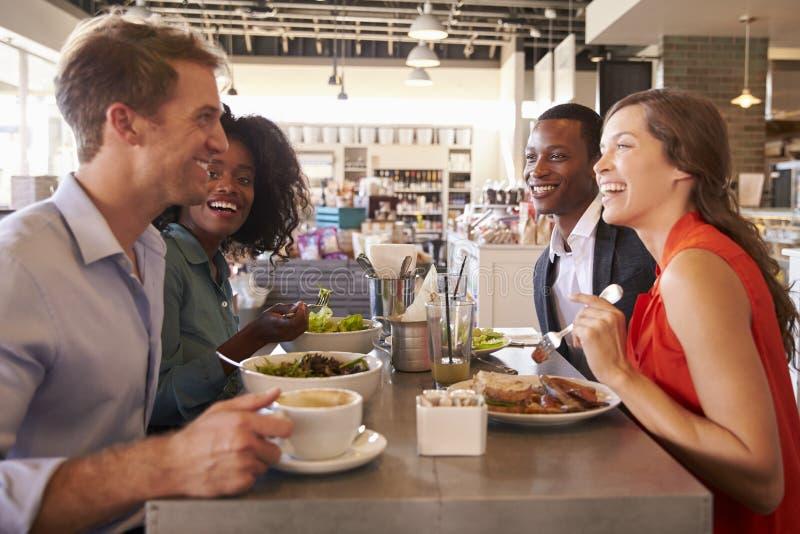 Gruppo che gode del pranzo di lavoro in specialità gastronomiche fotografia stock libera da diritti
