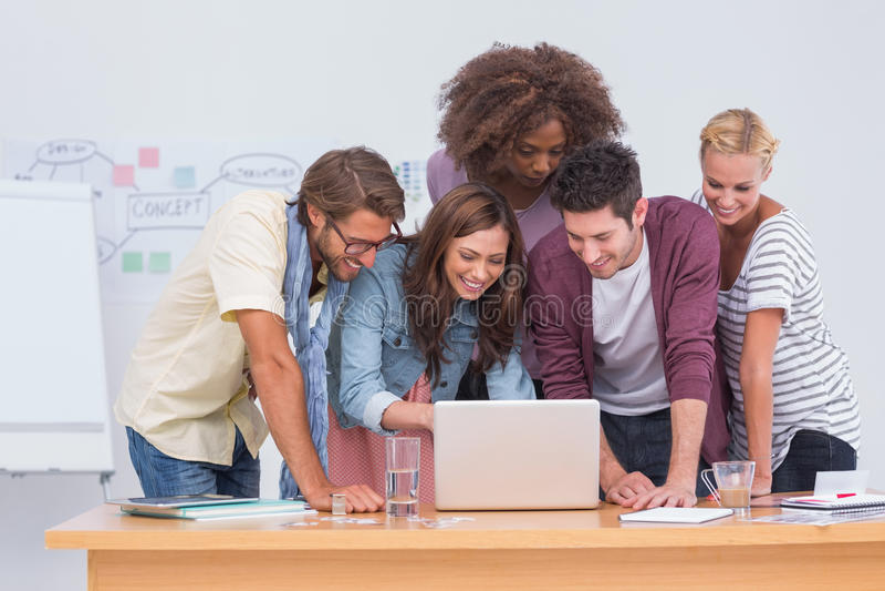 Gruppo creativo che esamina computer portatile fotografia stock