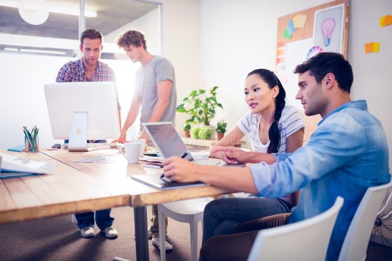 Gruppo creativo di affari riunito intorno ai computer portatili immagini stock libere da diritti