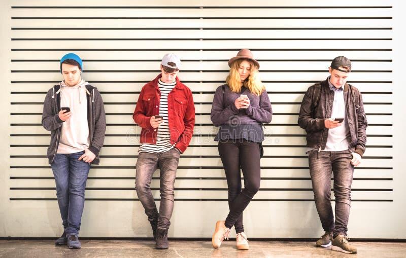 Gruppo degli amici che per mezzo dello smartphone contro la parete alla rottura del cortile dell'università - giovani dedicati da immagine stock