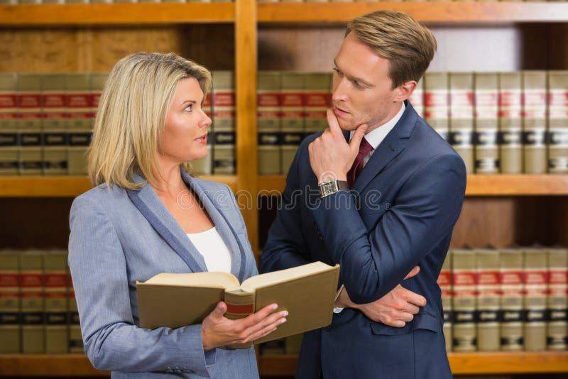 Gruppo degli avvocati nella biblioteca di legge immagine stock