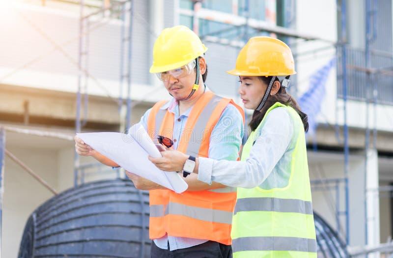 Gruppo degli ingegneri che indossano casco giallo e che lavorano alla costruzione immagini stock libere da diritti