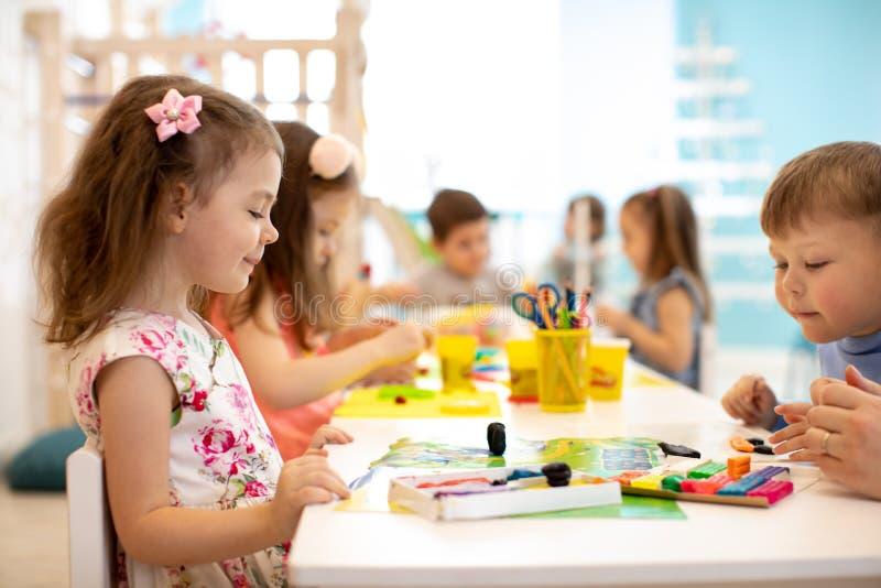 Gruppo dei bambini che impara le arti ed i mestieri in stanza dei giochi con interesse fotografie stock libere da diritti