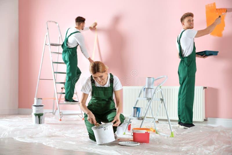 Gruppo dei decoratori professionisti che dipingono parete Servizio di riparazione domestico fotografia stock libera da diritti